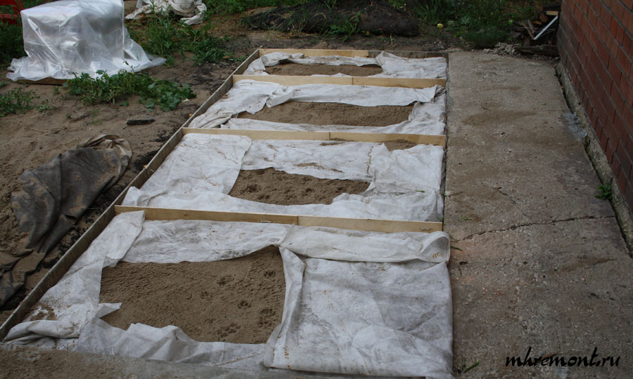 Сначала устраивается песчаная подушка, для этого на землю стелется агроволокно, затем насыпается песок и разравнивается, после чего края геотекстиля заворачиваются вовнутрь.