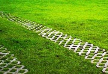 Альтернативой пластиковой решетки, которая довольно гибкая, служит бетонная решетка. Она более прочная, меньше скользит. Она может укладываться на предварительно выровненное основание или на песчаную подушку. Полости решетки засыпают землей и высаживают траву. Альтернативный вариант — это засыпка полости гравием.