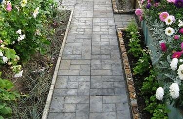 Проще и быстрее укладывать тротуарную плитку. Плитка стандартных размеров имеет размеры 30х30 см. Для большинства садовых тропинок достаточно укладывать две плитки вряд. Такой ширины дорожки будет достаточно для комфортной эксплуатации.