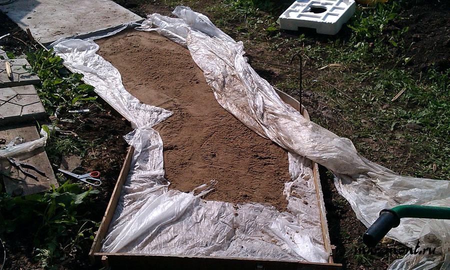 Слой песка составляет примерно 10 см. Остатки агроволокна можно загнуть на верх подушки. Перед началом заливки ее следует хорошо уплотнить. Самый простой способ это обильно пролить водой.