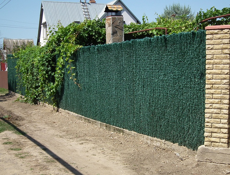 Обтянув прозрачный забор маскировочной сеткой можно легко скрыть участок от посторонних глаз.