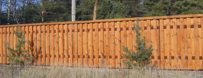 Глухой забор на даче можно изготовить, установив два ряда вертикальных досок. Такой вариант прекрасно подойдет для фасада участка.