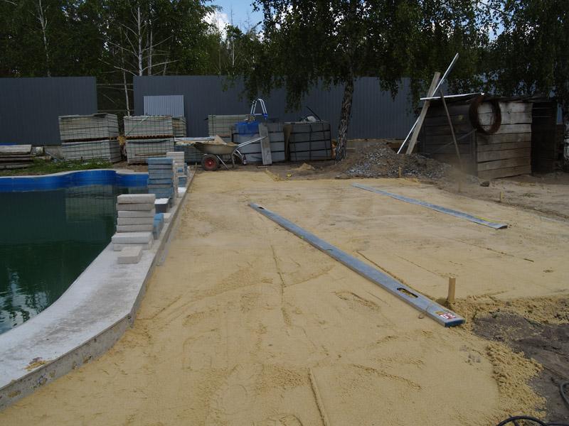 Тщательное разравнивание песка обеспечит ровную укладку плитки.