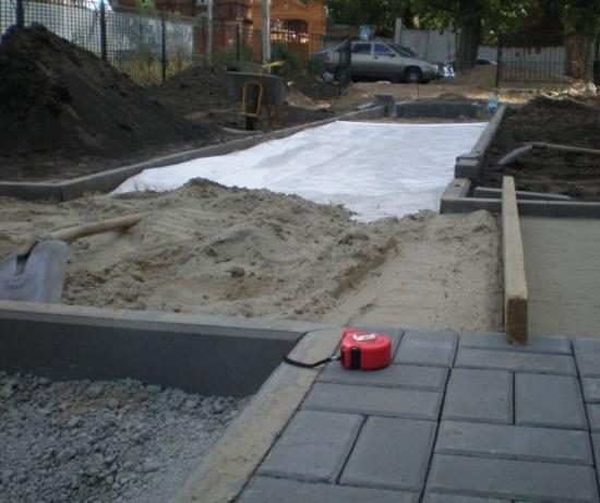 Между двумя рядами бордюрного камня настилают агроволокно. Оно предотвратит заиливание песка, таким образом будут сохранятся его дренажные качества. Поверх агроволокна насыпают влажный песок. Толщина песчаной подушки должна быть не менее 5 см.