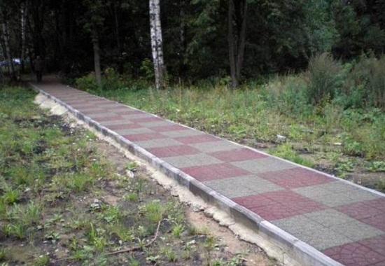 Укладка бордюров для тротуарной плитки должна выполняться на бетон. Дополнительно в раствор может быть уложена арматура. Таким образом крепить бордюрный камень особенно целесообразно если уровень тропинки выше уровня земли.