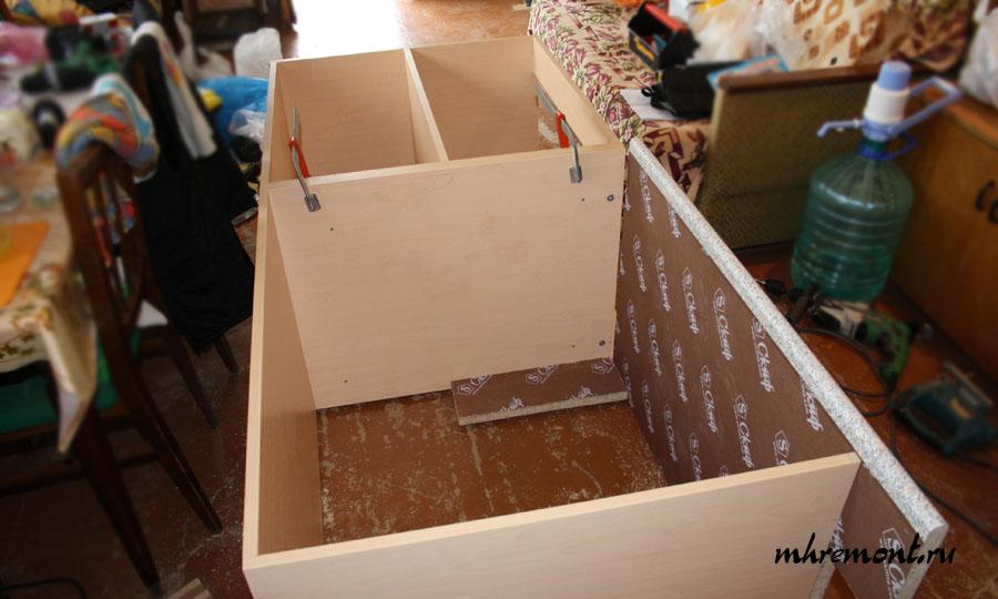 Шкаф под установку мойку изготавливается без верхних перекладин. Основу верхней части ящика выполняет столешница. Столешница крепится эксцентриковой стяжкой. Ящики стягиваются саморезами. Между двумя частями столешниц устанавливается специальная металлическая планка, которая защищает место соединения от попадания влаги.
