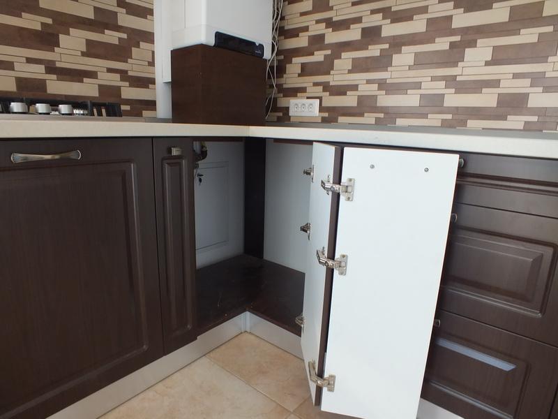 Особенность установки дверцы в угловой шкаф кухни. Применяются специальные петли.