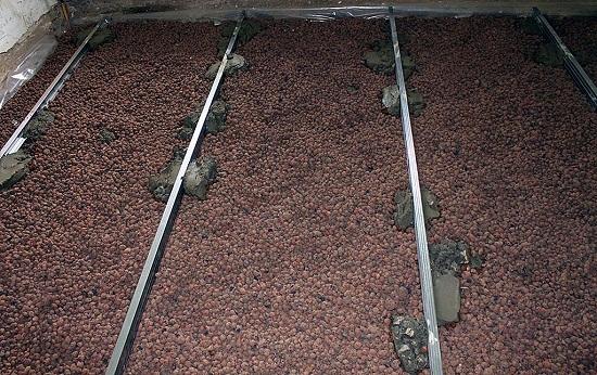 В качестве тепло и звуко изоляции можно насыпать слой керамзита. В случае необходимости сильно поднять уровень пола необязательно делать стяжку большой толщины. Толщины стяжки достаточно 50 мм, а остальное можно наполнить керамзитом.